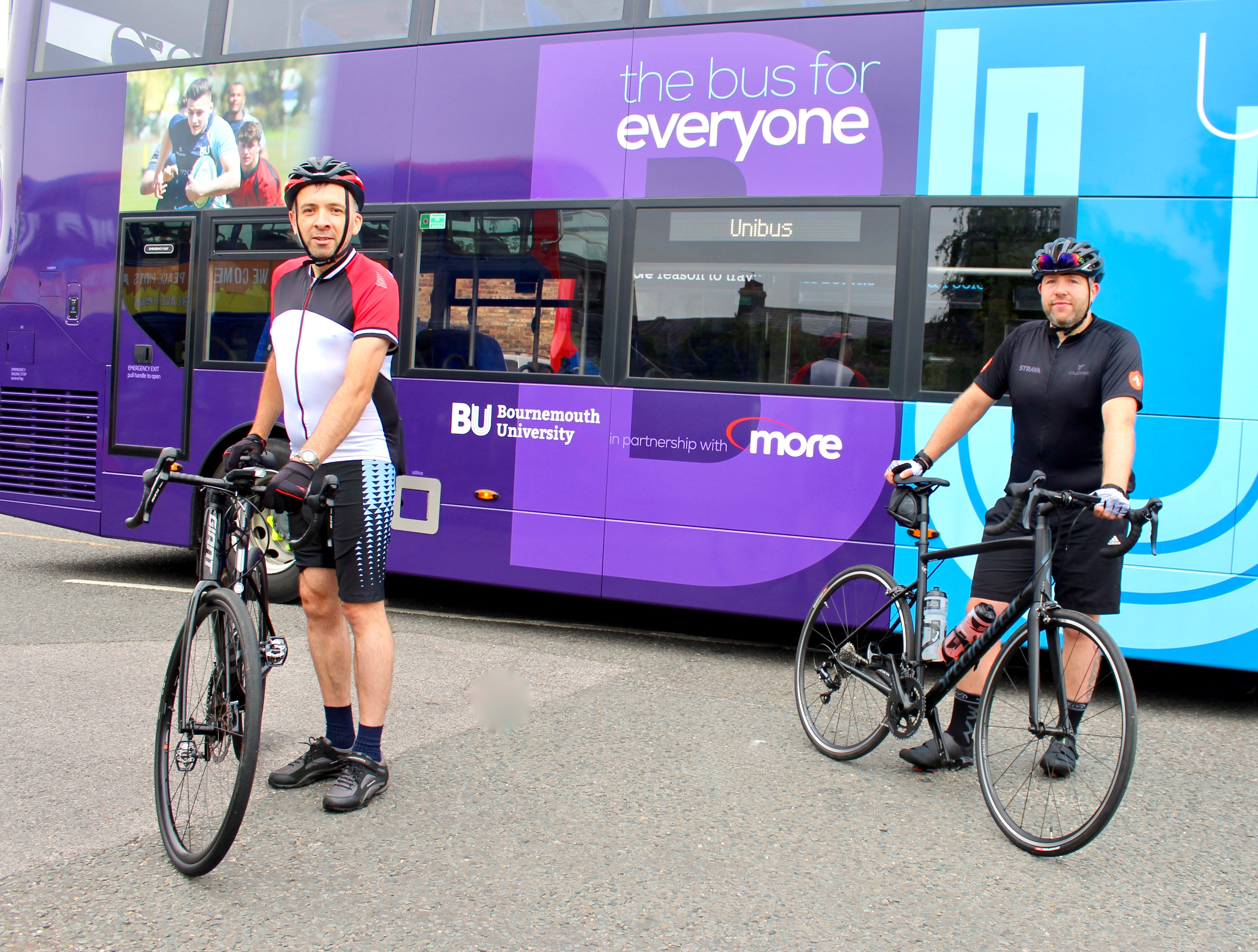 a photograph of martin and kris on their bikes in front of a bus